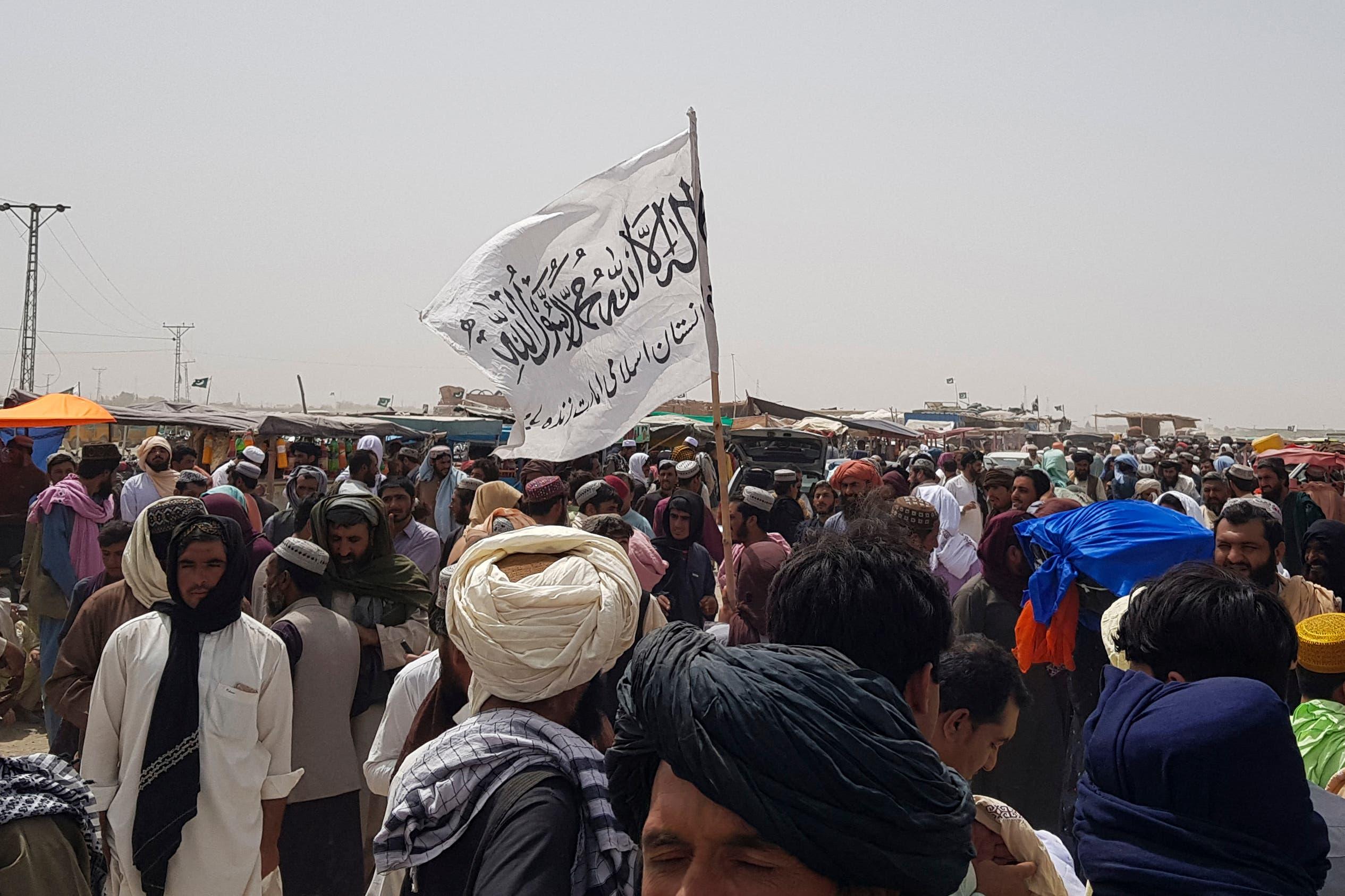 سكان في منطقة أفغانية قريبة من حدود باكستان يتجمعون حول علم طالبان بعد أنباء عن إفراجها عن السجناء