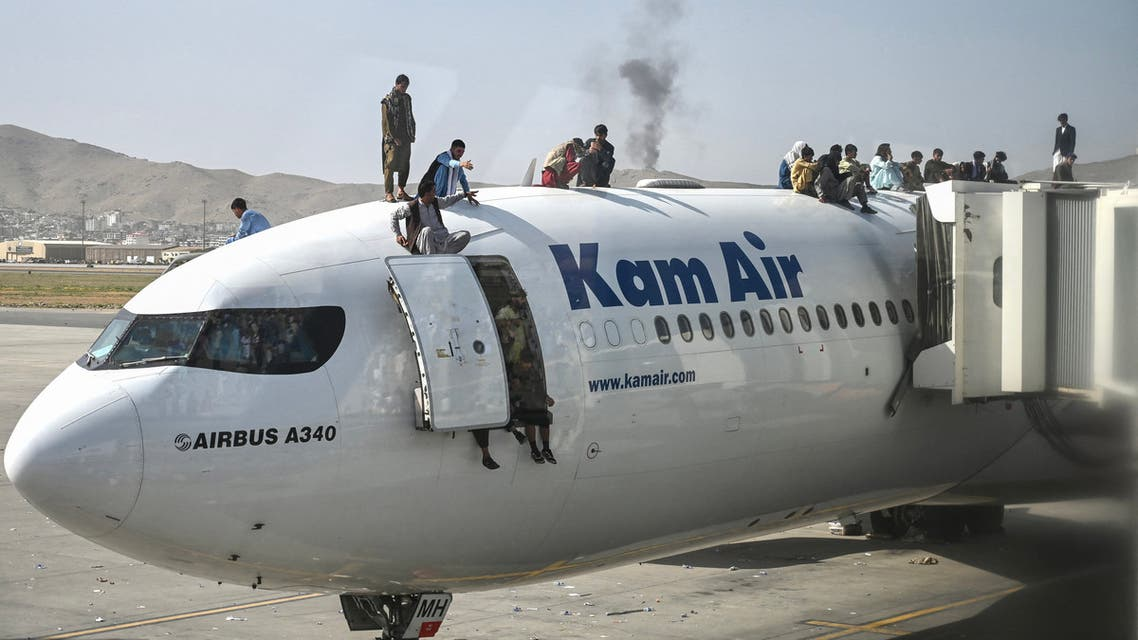 Afghan people climb atop a plane as they wait at the Kabul airport in Kabul on August 16, 2021. (File photo: AFP)