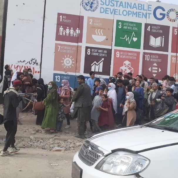 شاهد.. مقاتل طالباني يحتجز نساء وأطفالا أمام لوحة أممية