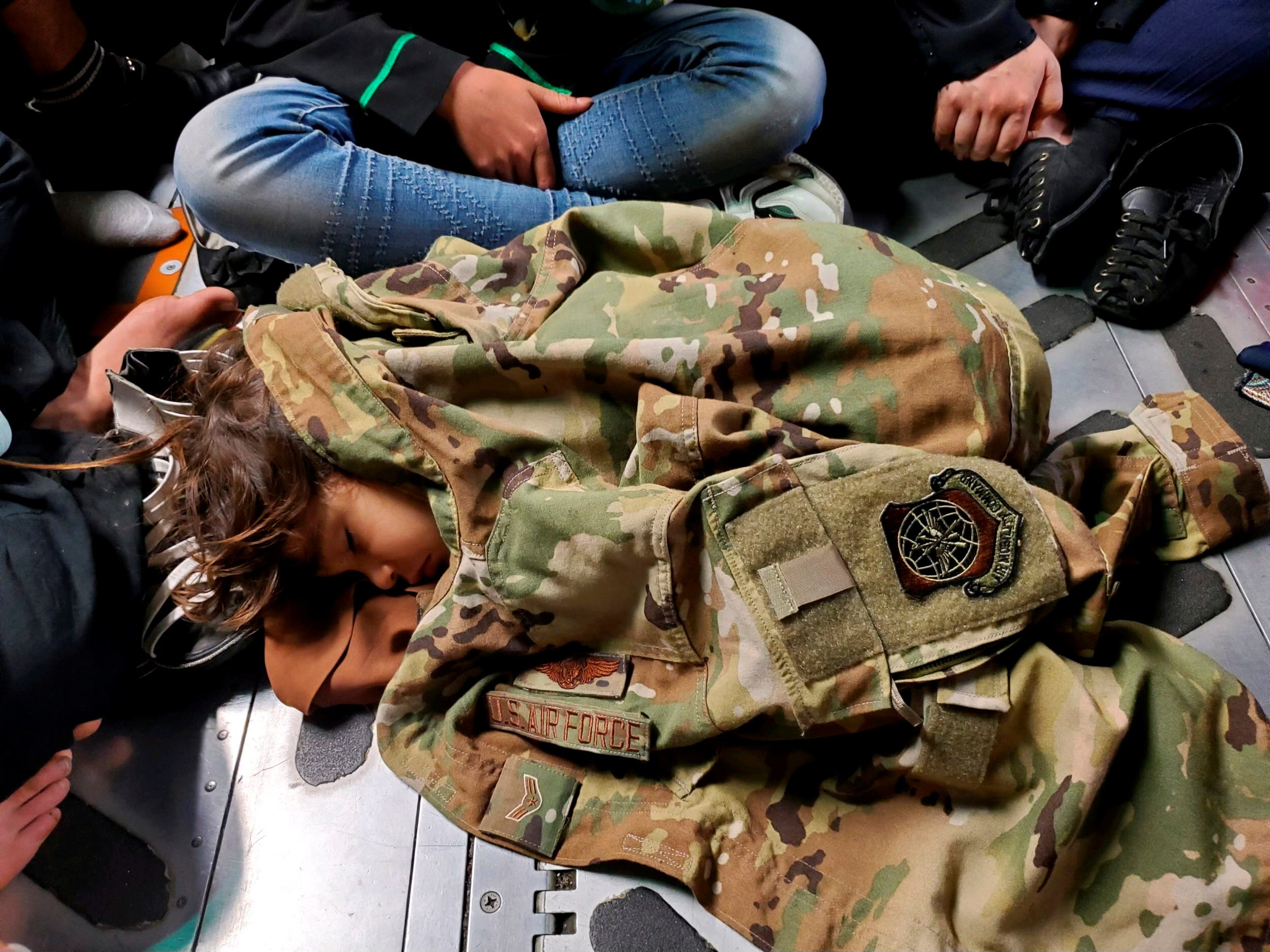 An Afghan child sleeps on the cargo floor of a US Air Force C-17 Globemaster III, kept warm by the uniform of Airman First Class Nicolas Baron, C-17 loadmaster, during an evacuation flight from Kabul, Afghanistan, August 18, 2021. (Reuters)