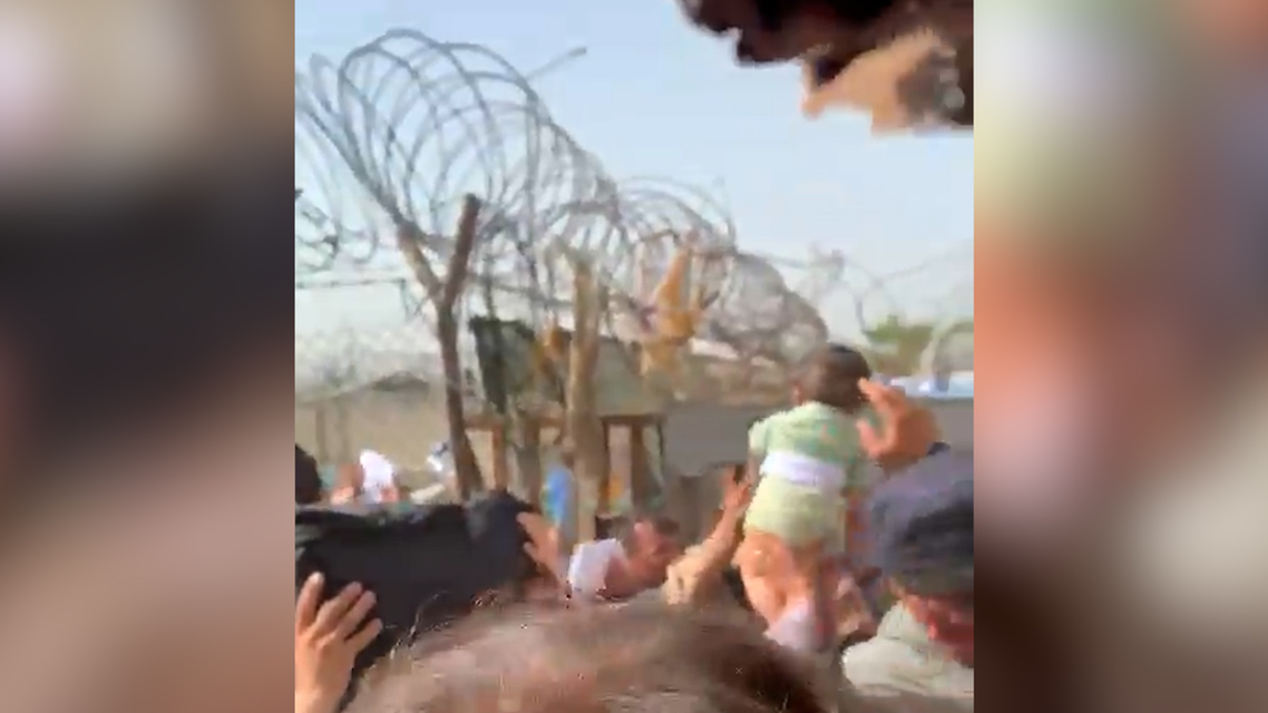 Screengrab from a video showing an Afghan trying to hand a baby to soldiers at Kabul airport. (Twitter)