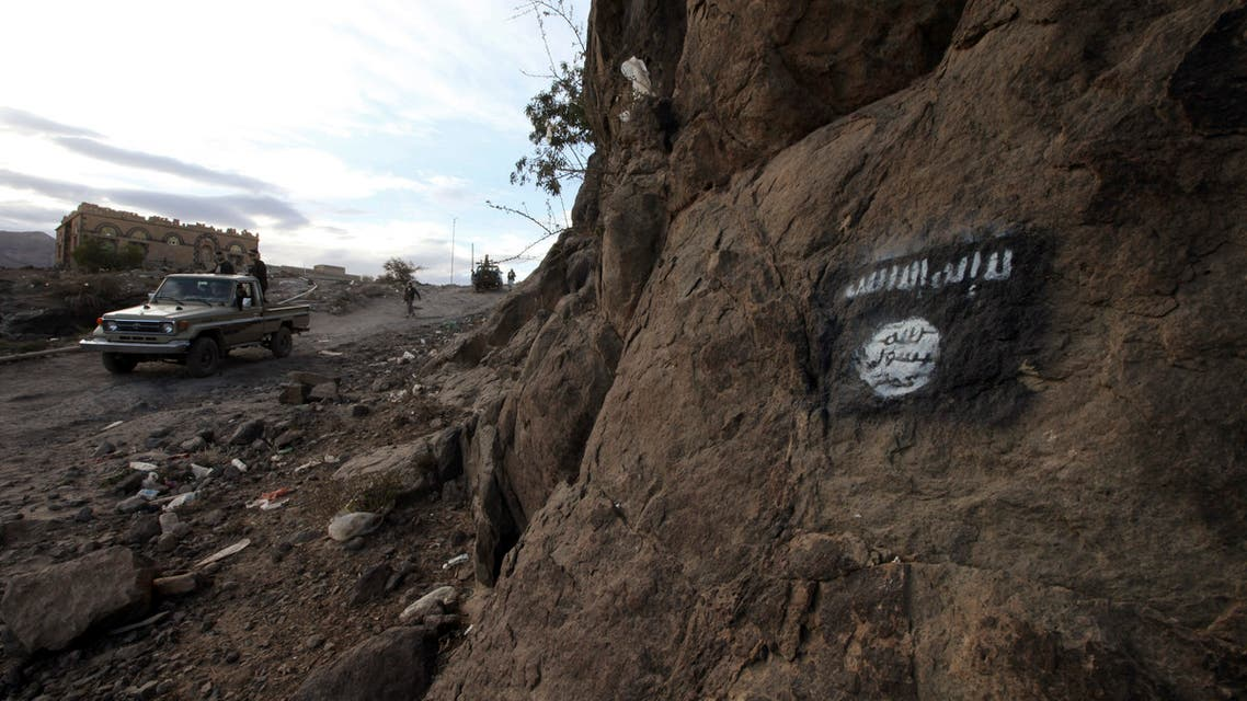 Iran-backed Houthi rebels drive a patrol truck past a flag of Ansar al-Sharia, the local wing of Al Qaeda in the Arabian Peninsula (AQAP), painted on the side of a hill, along a road in Almnash, the main stronghold of Ansar al-Sharia, in Rada, Yemen, November 22, 2014. (Reuters)
