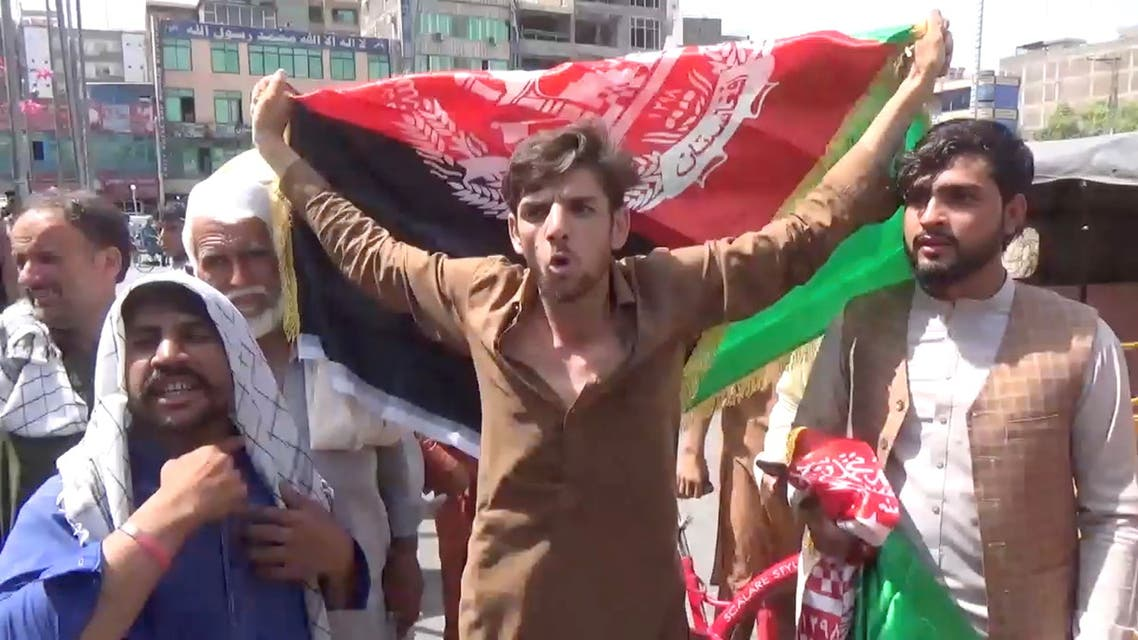 People carry Afghan flags as they take part in an anti-Taliban protest in Jalalabad, Afghanistan August 18, 2021 in this screen grab taken from a video. (Reuters)
