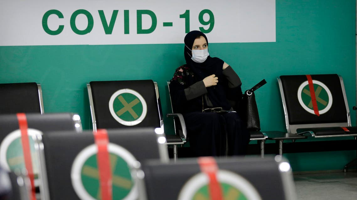 A woman waits to receive her first dose of the Pfizer coronavirus vaccine at a vaccination center, at the old Jiddah airport, Saudi Arabia, Tuesday, May 18, 2021. (AP)