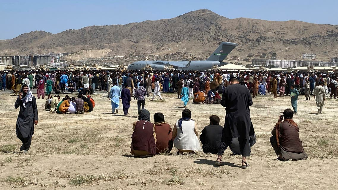 Hundreds of people gather near a U.S. Air Force C-17 transport plane at the perimeter of the international airport in Kabul, Afghanistan, Monday, Aug. 16, 2021. (AFP)