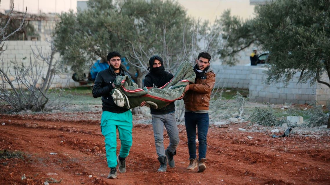 Syrian men carry a child's body after airstrikes destroyed his family house at the northern town of Sarmin, in Idlib province, Syria, on Feb. 2, 2020. (AP)