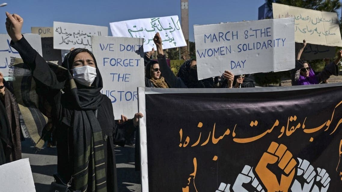 Women demonstrators hold banners as they march toward to the governor office during a peaceful protest to mark International Women's Day in Herat on March 8, 2021. (AFP)