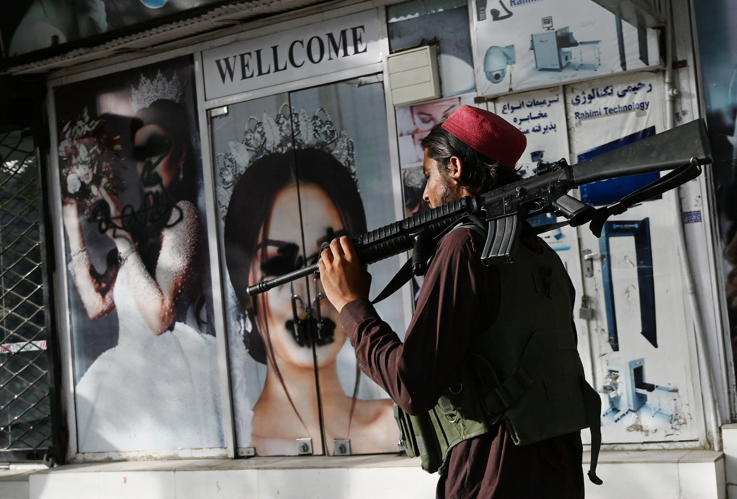 A Taliban fighter walks past a beauty salon with images of women defaced using spray paint in Shar-e-Naw in Kabul on August 18, 2021. (File photo: AFP)