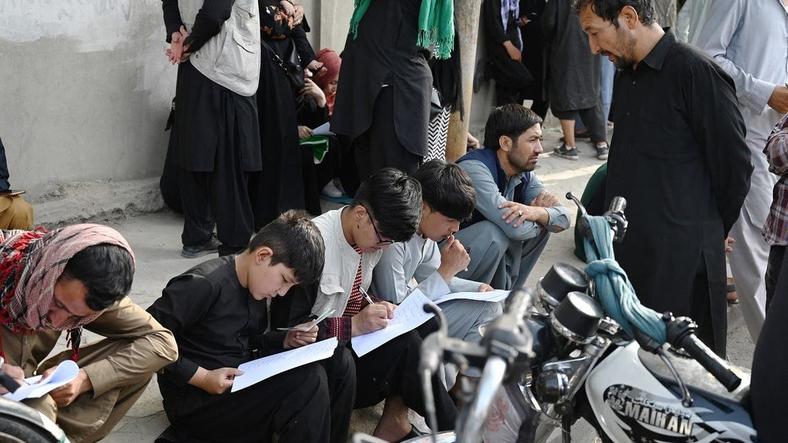 Afghan people fill up their details on a sheet of paper to register their name in order to leaves the country in front of the British and Canadian embassy in Kabul on August 19, 2021 after Taliban's military takeover of Afghanistan. (AFP)