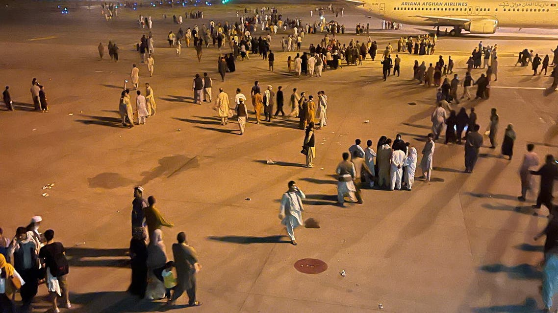 An undated amateur picture obtained by Reuters on August 19, 2021 shows people walking on the tarmac of the airport in Kabul, Afghanistan. (Reuters)