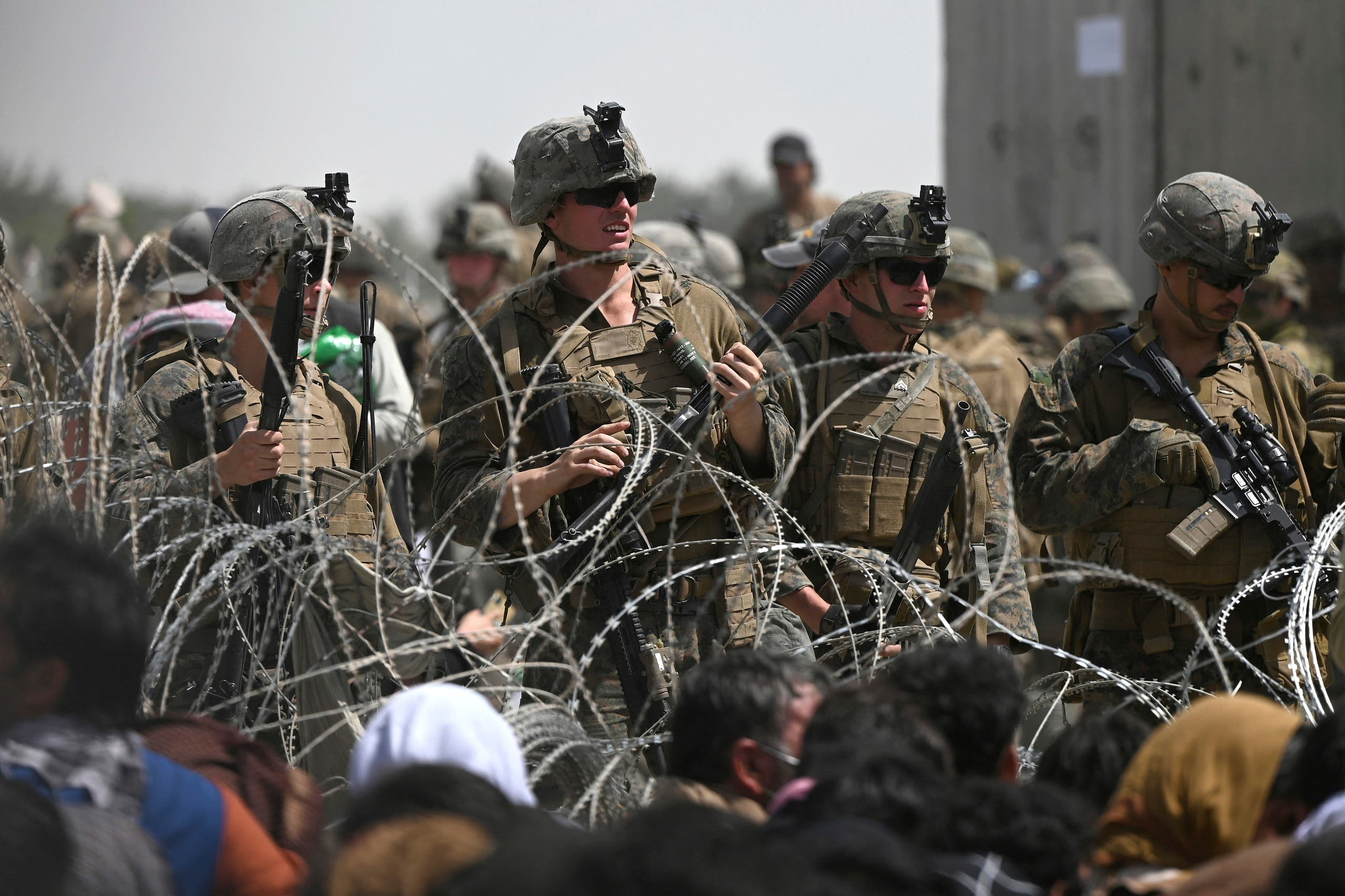 US soldiers stand guard behind barbed wire as Afghans sit on a roadside near the military part of the airport in Kabul on August 20, 2021, hoping to flee from the country after the Taliban's military takeover of Afghanistan. (AFP)