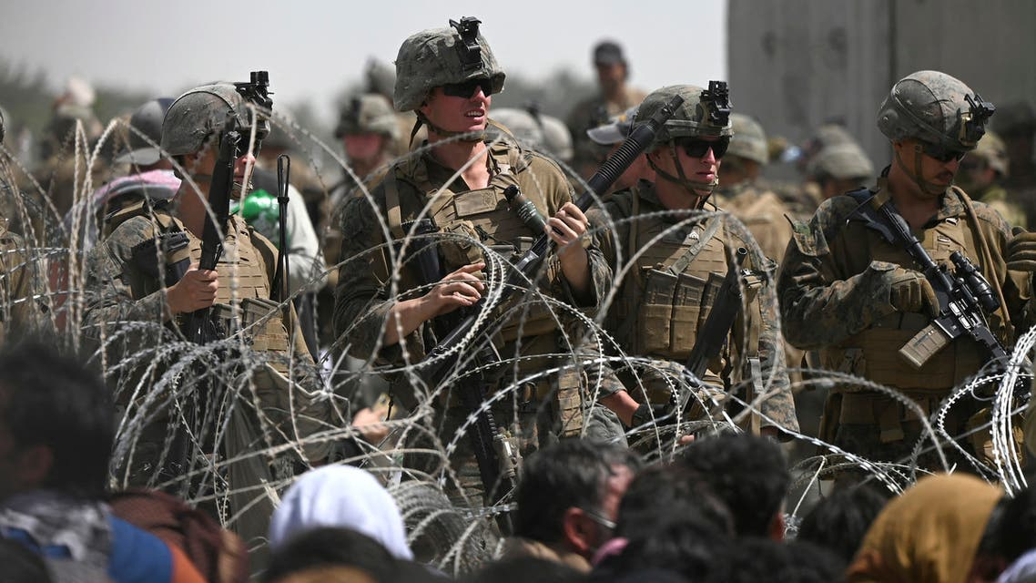 US soldiers stand guard behind barbed wire as Afghans sit on a roadside near the military part of the airport in Kabul on August 20, 2021, hoping to flee from the country after the Taliban's military takeover of Afghanistan. Wakil KOHSAR / AFP