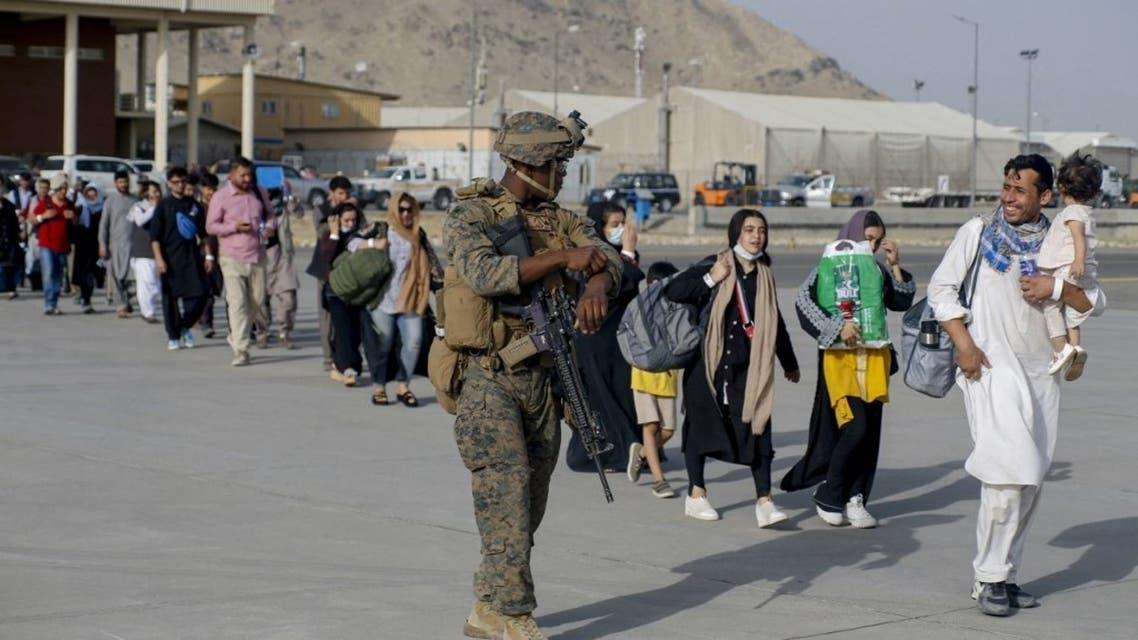 جندي أميركي وعائلات أفغانية تستعد للإجلاء من مطار كابل بعد سيطرة طالبان - فرانس برس
