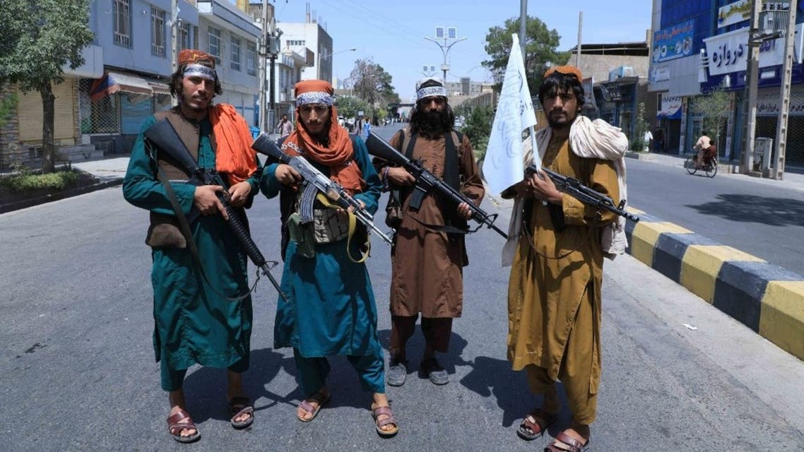 Taliban fighters stand guard along a road near the site of an Ashura procession which is held to mark the death of Imam Hussein, the grandson of Prophet Mohammad, along a road in Herat on August 19, 2021. (AFP)