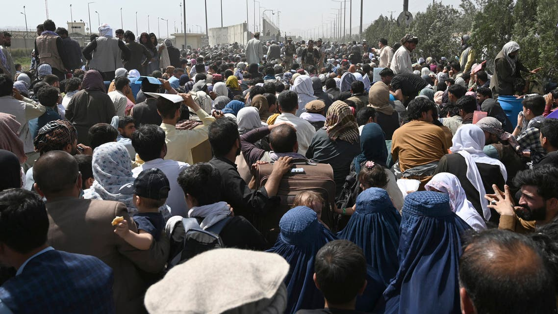 Afghans gather on a roadside near the military part of the airport in Kabul on August 20, 2021, hoping to flee from the country after the Taliban's military takeover of Afghanistan. (AFP)