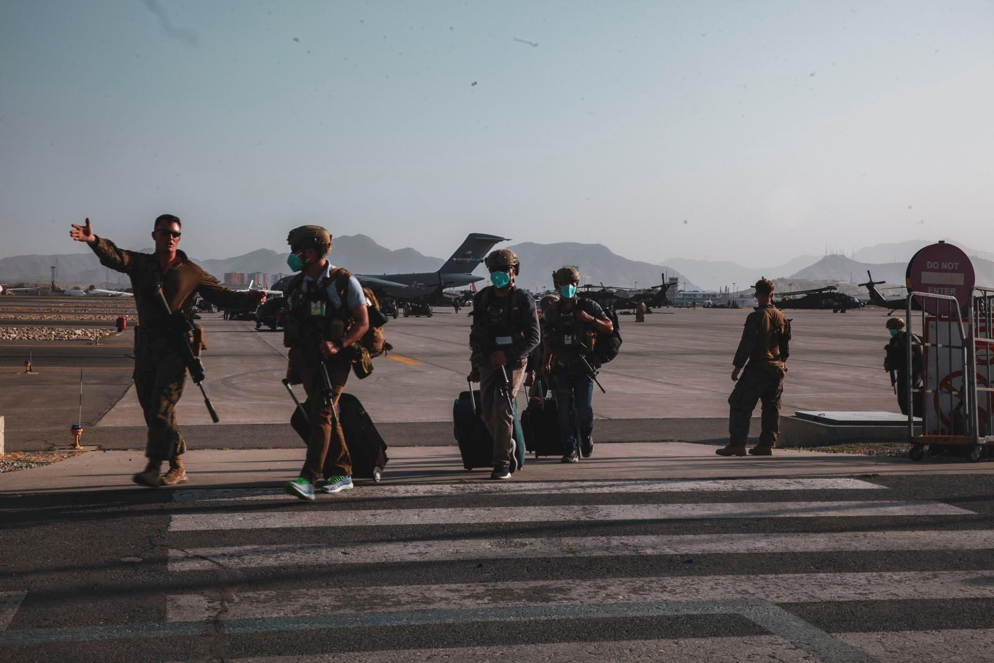 أحد أفراد مشاة البحرية الأميركية يرافق أفراد وزارة الخارجية من أجل الإجلاء في مطار حامد كرزاي الدولي بكابل (أرشيفية من رويترز)