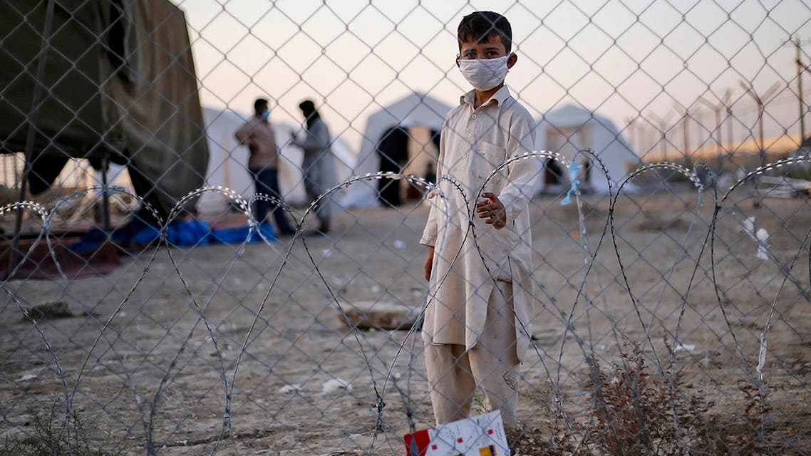 A handout picture made available by the Iranian Red Crescent on August 19, 2021, shows a young Afghan refugee at the Iran-Afghanistan border between Afghanistan and the southeastern Iranian Sistan and Baluchestan province, as people fleeing Afghanistan try to enter the Islamic republic following the takeover of their country by the Taliban earlier this week. (File photo: AFP)