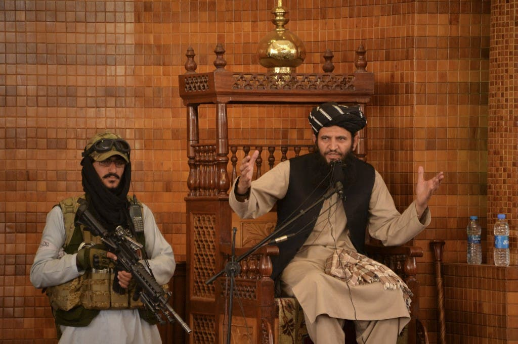 An Imam speaks next to an armed Taliban fighter during Friday prayers at the Abdul Rahman Mosque in Kabul on August 20, 2021. (AFP)