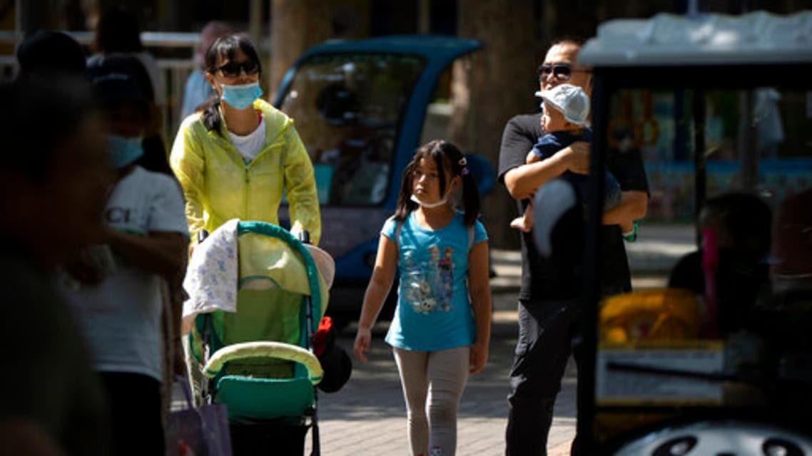 Adults and children walk along a path at a public park in Beijing, Saturday, Aug. 21, 2021.  (AP)