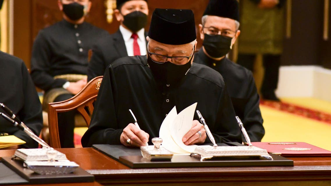 In this photo released by Malaysia's Department of Information, Malaysia's new Prime Minister Ismail Sabri Yaakob, signs documents after taking the oath as the country's new leader at the National Palace in Kuala Lumpur. (AP)