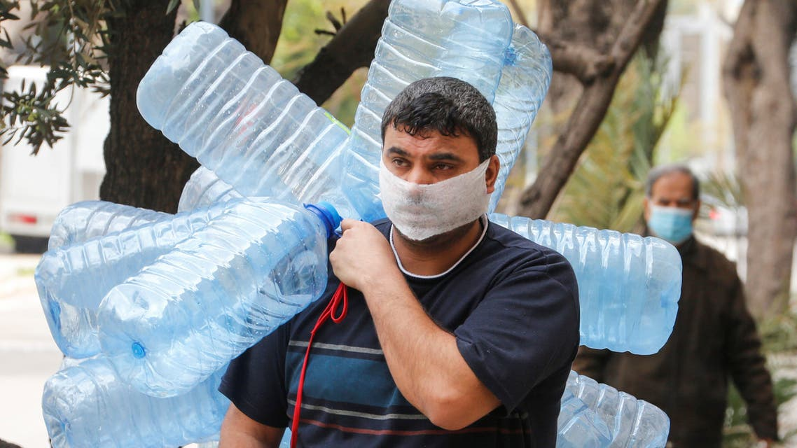 A man covers his face with a makeshift mask as he carries empty gallons of water, during a lockdown to prevent the spread of coronavirus disease (COVID-19) in Beirut, Lebanon April 6, 2020. (Reuters)