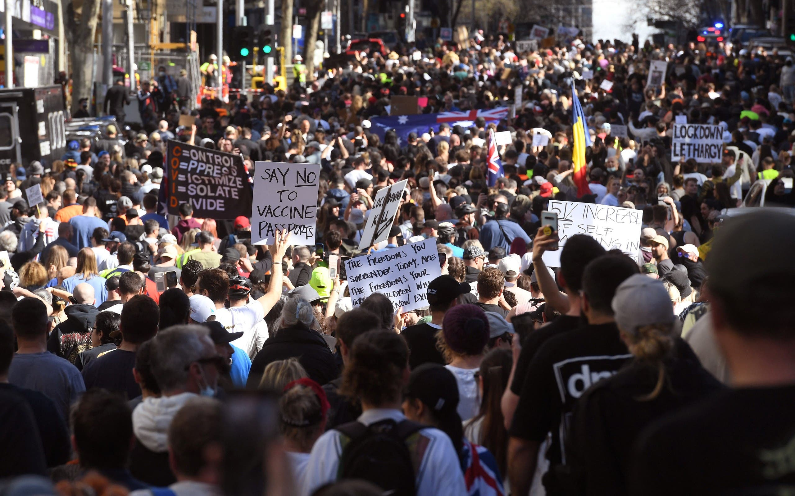 Protesters march through the streets during an anti-lockdown rally in Melbourne on August 21, 2021 as the city experiences it's sixth lockdown while it battle an outbreak of the Delta variant of coronavirus. (AFP)