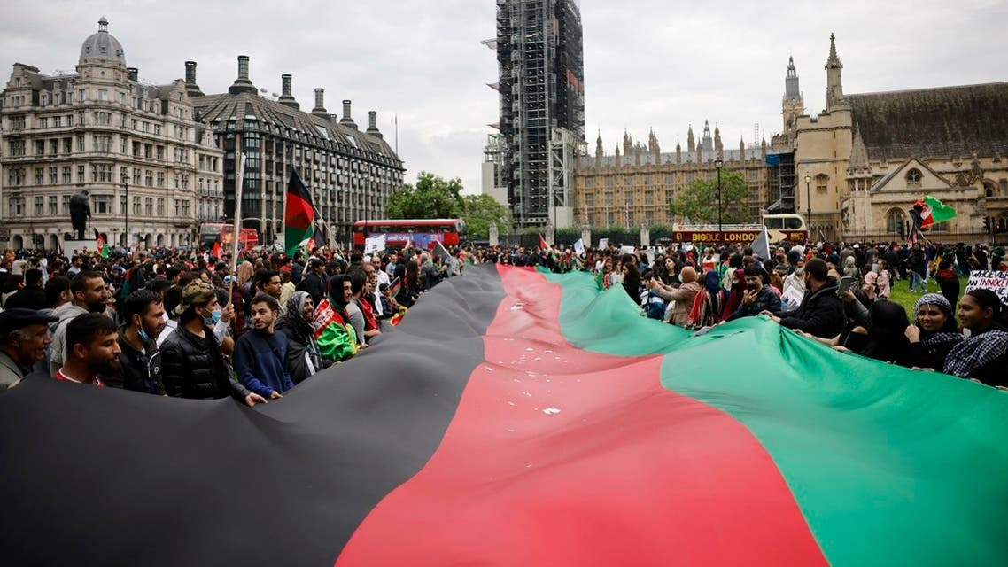 Protesters display a giant Afghan flag as they demonstrate in solidarity with the people of Afghanistan, in Parliament Square, central London on August 21, 2021. (Tolga Akmen/AFP)