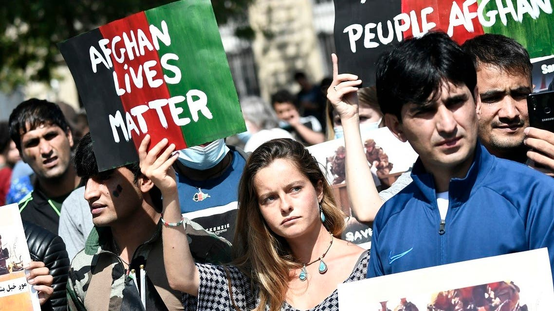Protesters hold banners during a rally in support for Afghanistan following the take-over of the country by the Taliban, at Place de la Republique in Paris on August 22, 2021. (Stephane De Sakutin/AFP)