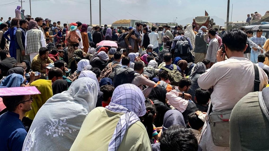 Afghan people gather along a road as they wait to board a US military aircraft to leave the country, at a military airport in Kabul on August 20, 2021 days after Taliban's military takeover of Afghanistan. (Wakil Kohsar/AFP)