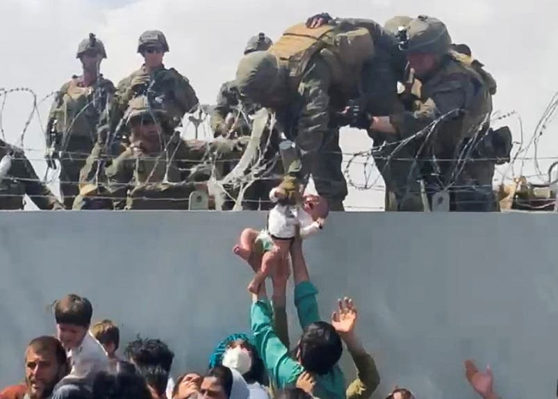 A baby is handed over to the American army over the perimeter wall of the airport for it to be evacuated, in Kabul, Afghanistan, August 19, 2021. (Reuters)