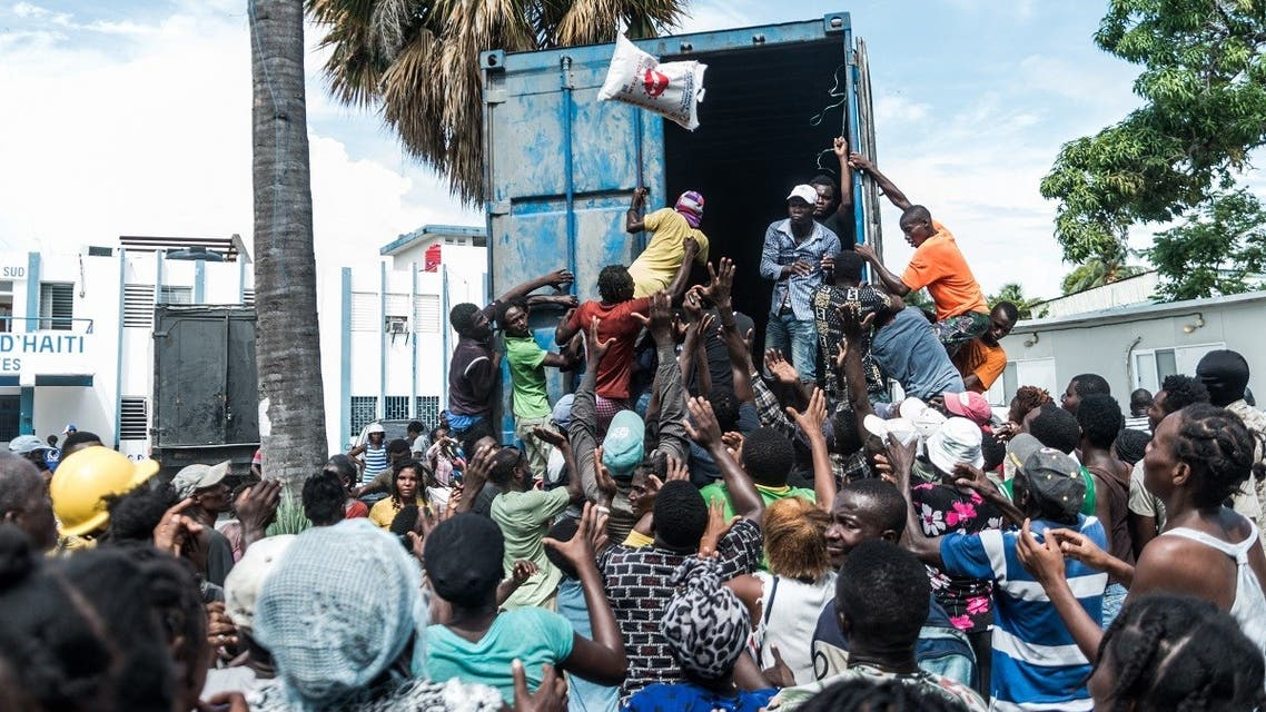 """A man throws a bag of rice into a crowd of earthquake victims gathered for the distribution of food and water at the """"4 Chemins"""" crossroads in Les Cayes, Haiti on August 20, 2021. (Reginald Louissaint JR/AFP)"""