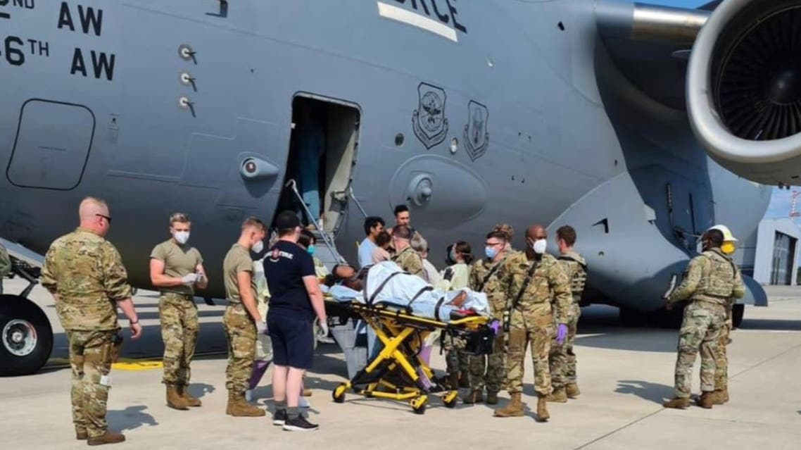 Medical support personnel from the 86th Medical Group help an Afghan mother and family off a US Air Force C-17 moments after she delivered a child aboard the aircraft upon landing at Ramstein Air Base, Germany. (Twitter)
