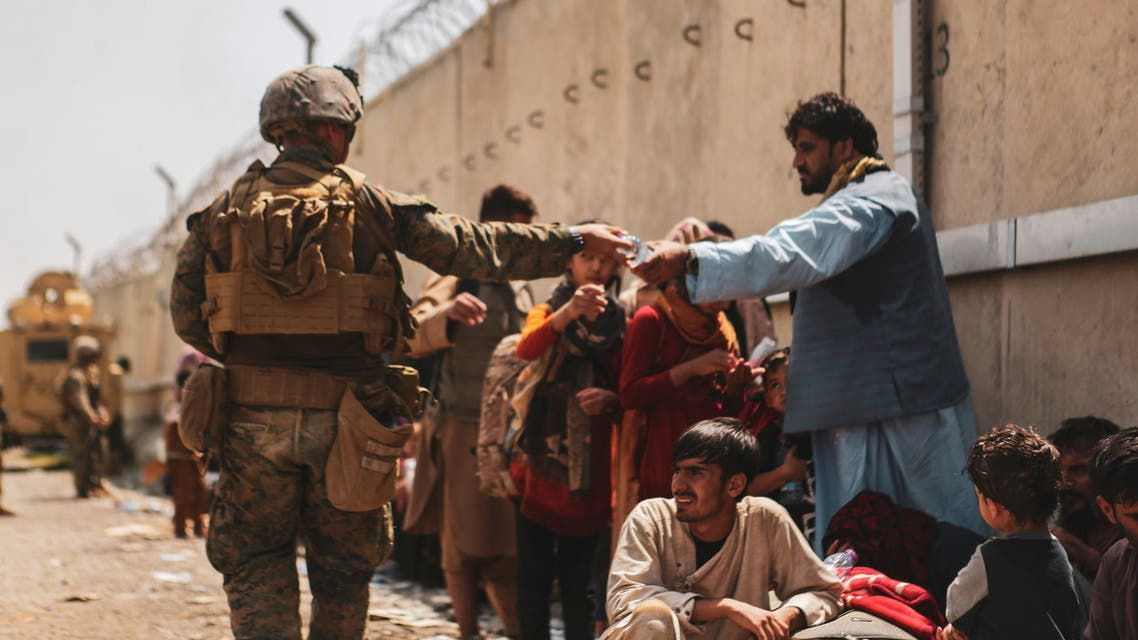 A US Marine passes out water to evacuees during an evacuation at Hamid Karzai International Airport, Aug. 22, 2021. (Reuters)