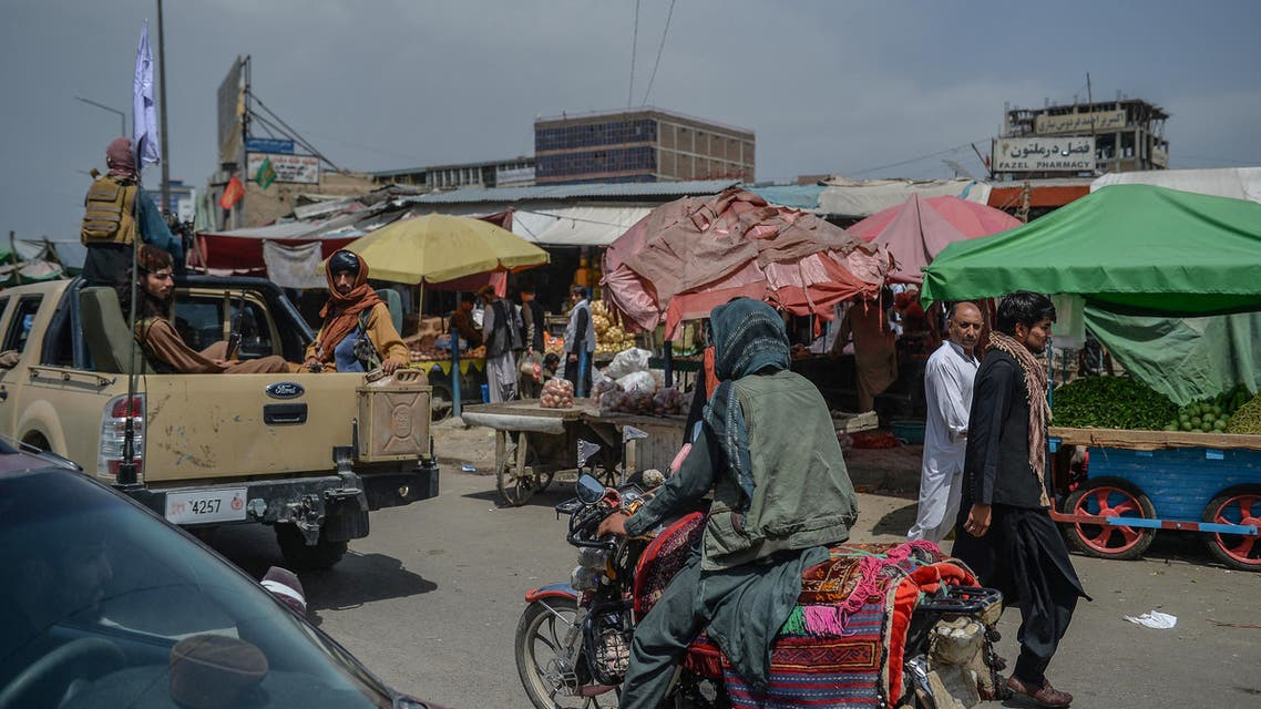 Taliban fighters on a pick-up truck (L) move around a market area, flocked with local Afghan people at the Kote Sangi area of Kabul on August 17, 2021, after Taliban seized control of the capital following the collapse of the Afghan government.