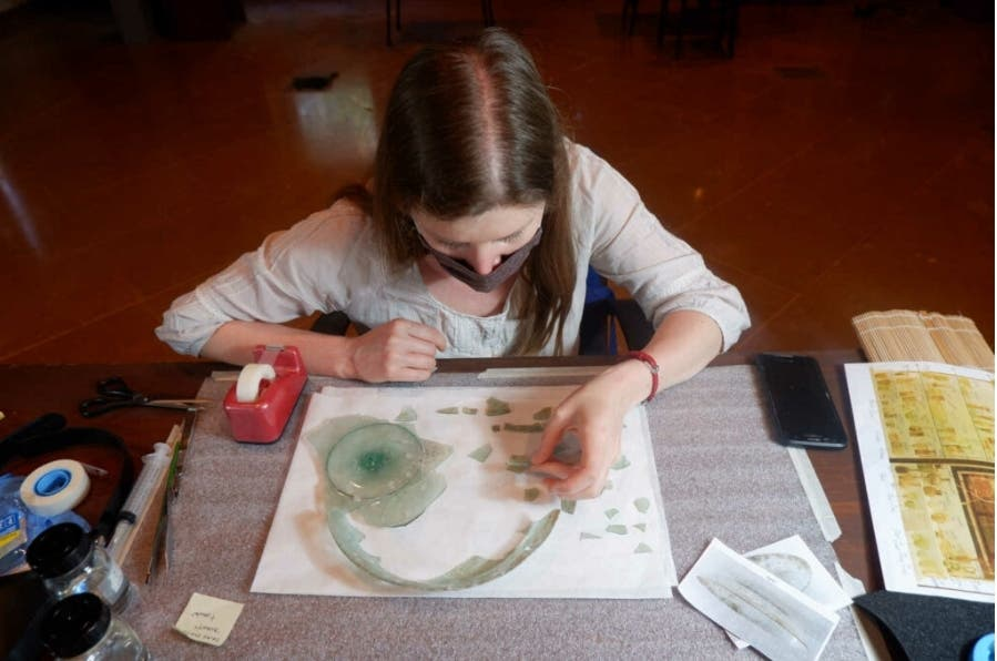 Claire Cuyaubère a specialist conservator sent by the French National Institute of Cultural Heritage to analyze the shattered glass artifacts engages in the process of puzzle work. (Supplied)