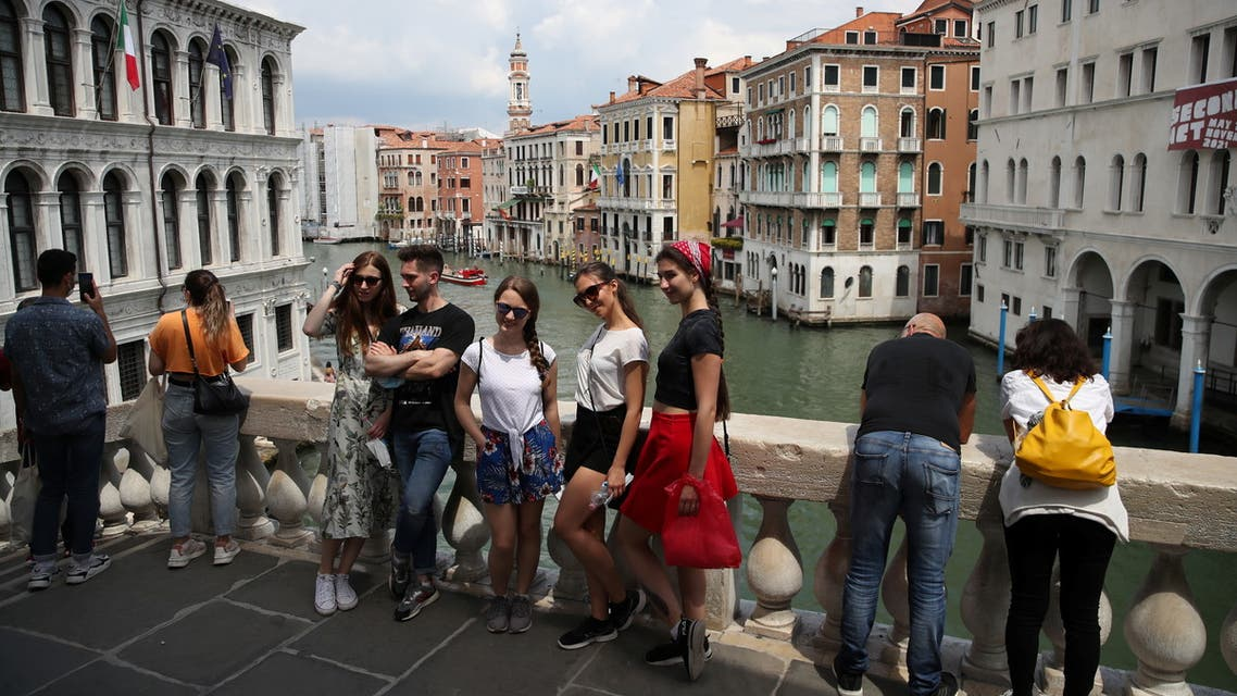 Tourists pose for a picture at the Rialto Bridge, as the region of Veneto becomes a white zone, following a relaxation of COVID-19 restrictions with only masks and social distancing required, in Venice, Italy, June 7, 2021. (File photo: Reuters)