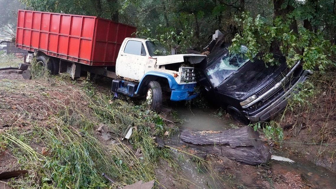 A truck and a car sit in a creek August 22, 2021, after they were washed away the day before in McEwen, Tennessee. (AP /Mark Humphrey)