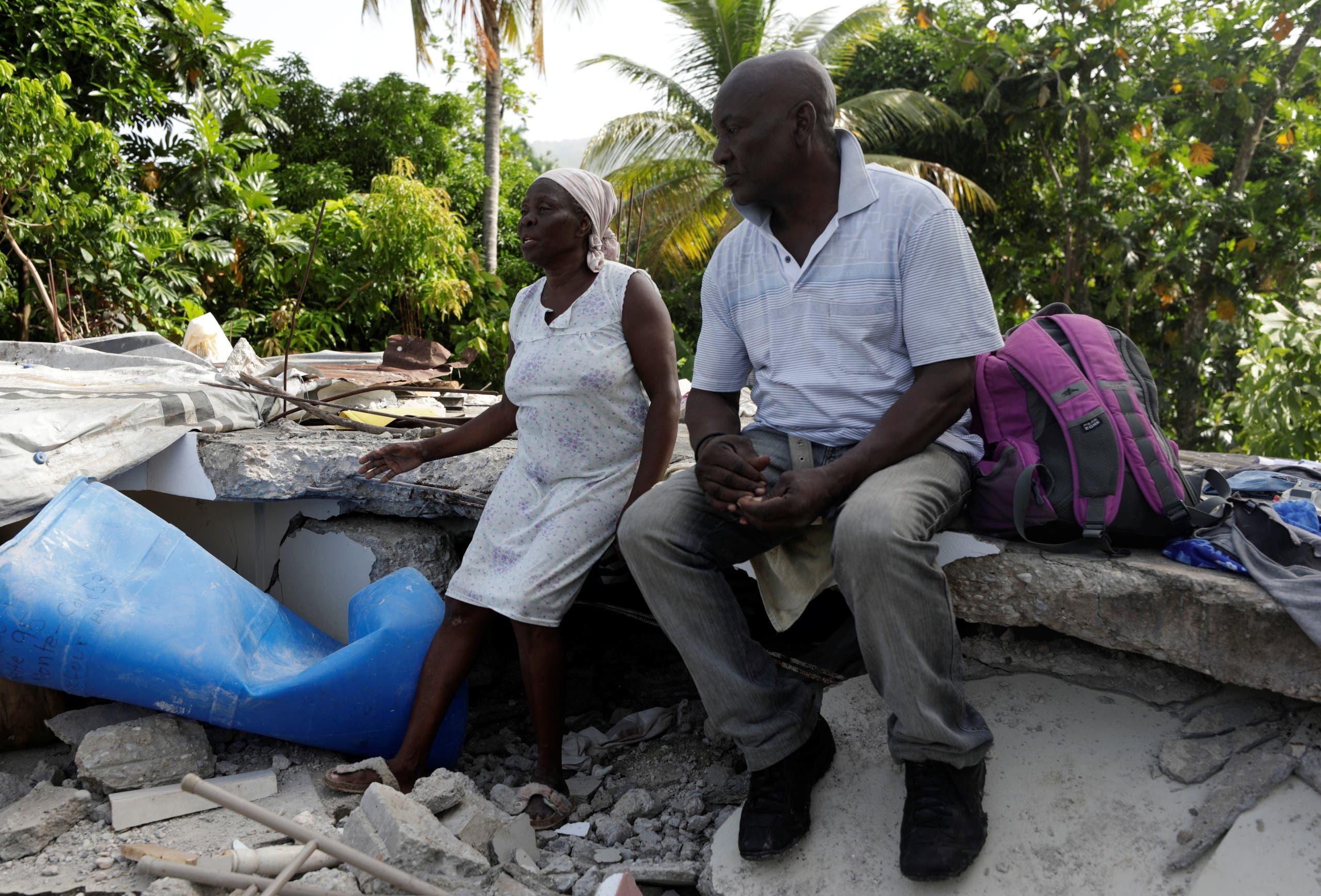 رجل وزوجته يجلسان على ركام منزلهما الذين دمره الزلزال