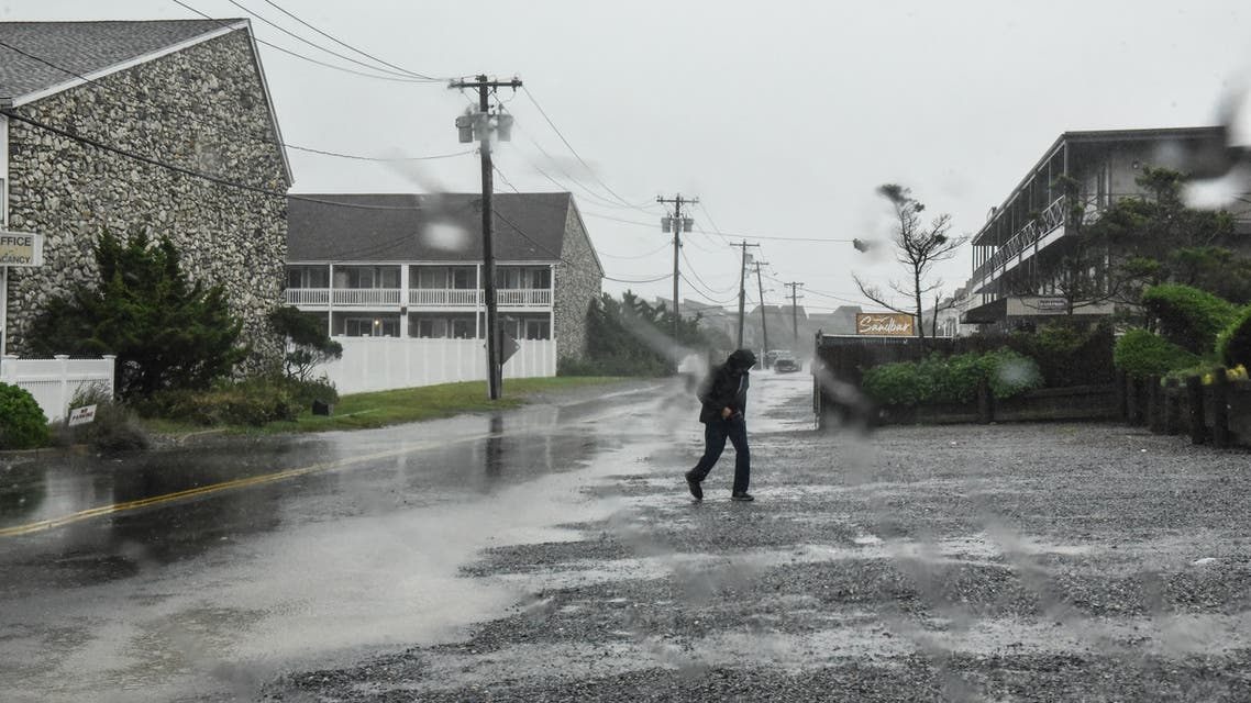 MONTAUK, NY - AUGUST 22: A person walks across the street on August 22, 2021 in Montauk, New York. Tropical Storm Henri was downgraded from a Category 1 Hurricane on Sunday morning as heavy rain pounded the east end of Long Island. Stephanie Keith/Getty Images/AFP