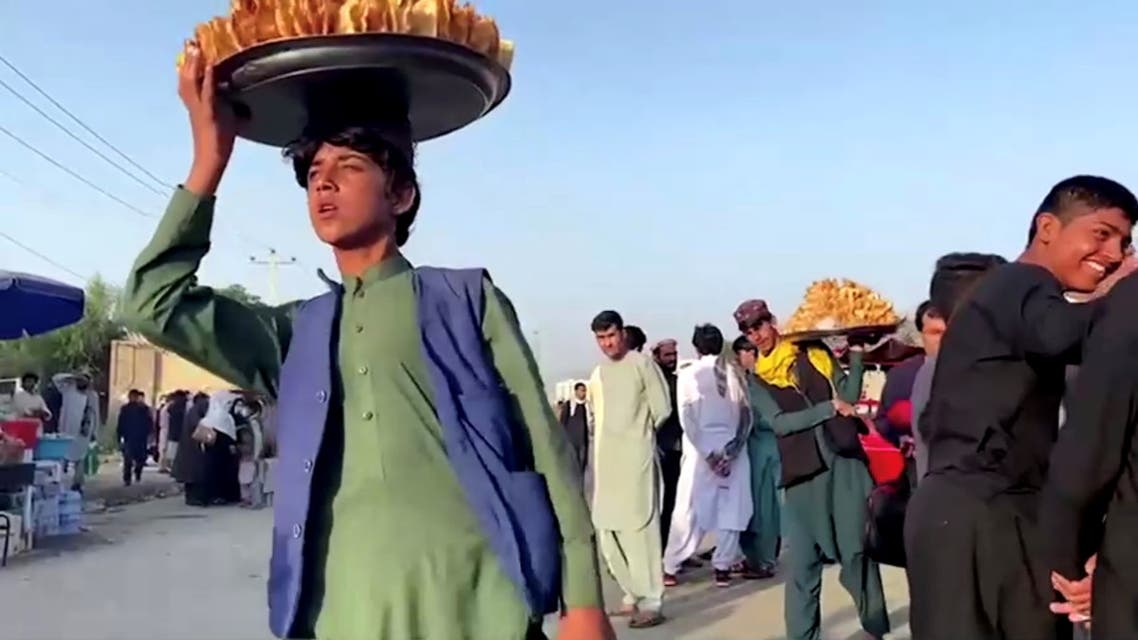 Vendors carry trays with food outside Kabul airport, Afghanistan, August 22, 2021 in this still image taken from video. REUTERS/ReutersTV