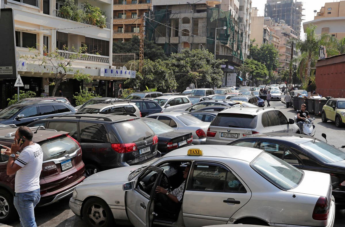 Lebanese wait in a queue outside a closed petrol station in Beirut's Hamra district on August 20, 2021. (Anwar Amro/AFP)