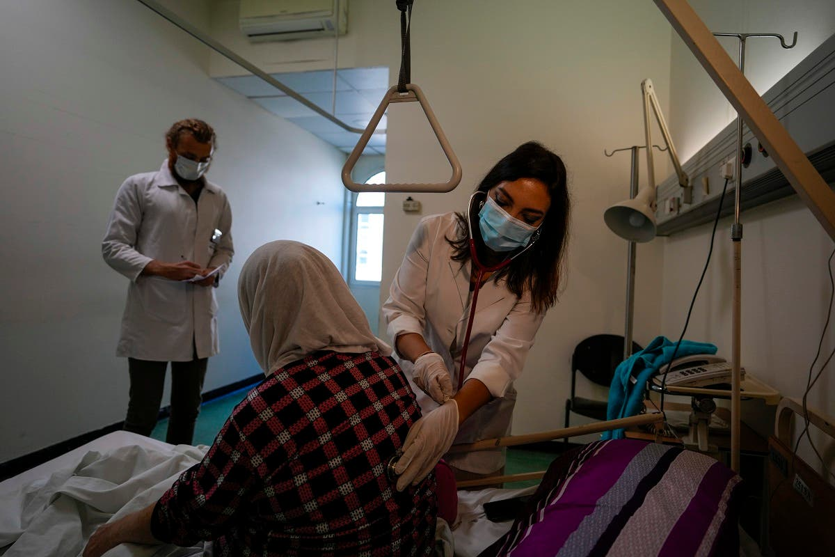 Ghaidaa al-Saddik, internal medicine resident doctor checks on a patient at government-run Rafik Hariri University Hospital in Beirut, Lebanon, Wednesday, Aug. 11, 2021. (AP/Hassan Ammar)
