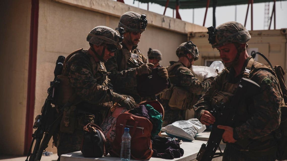 Marines with the 24th Marine Expeditionary Unit (MEU) search luggage during an evacuation at Hamid Karzai International Airport, Kabul, Afghanistan, in this photo taken on August 18, 2021 and released by U.S. Navy on August 20, 2021. (Reuters)
