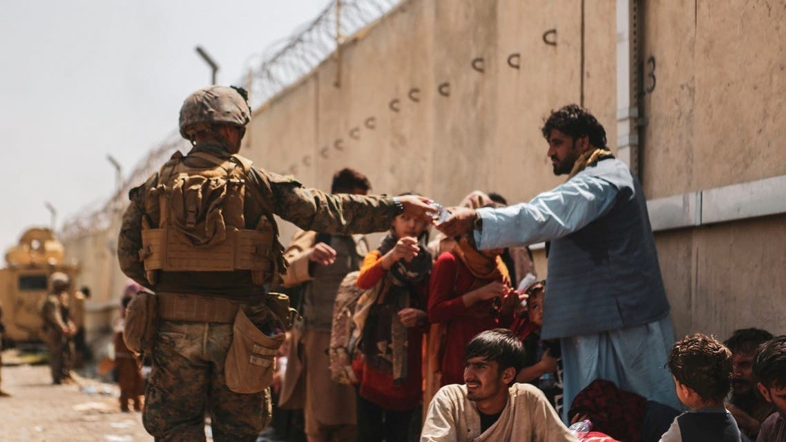 A U.S. Marine passes out water to evacuees during an evacuation at Hamid Karzai International Airport, Kabul, Afghanistan, August 22, 2021. (Reuters)