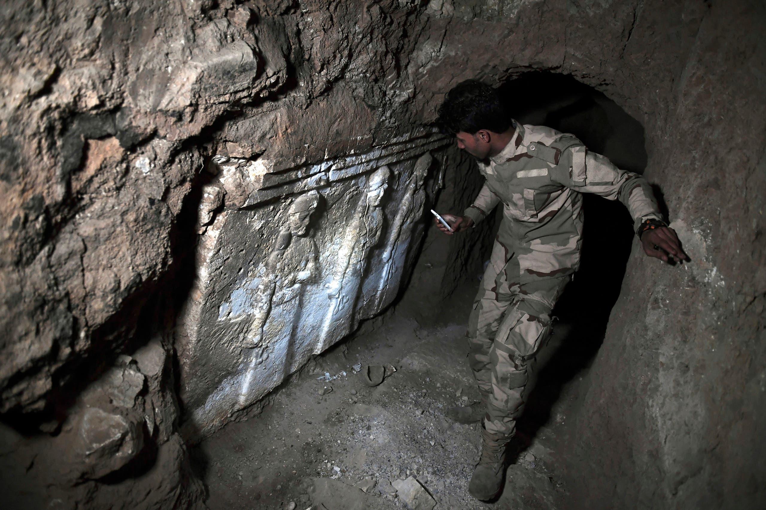 جندي عراقي يتفقد أحد الأنفاق لتهريب الآثار (أرشيفية- فرانس برس)