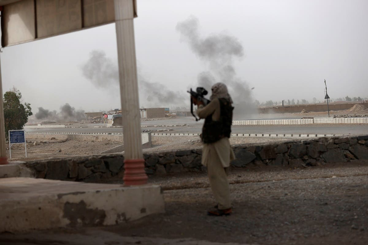 An Afghan soldier holds a gun and looks towards Taliban positions as smoke rises in the distance from clashes on the outskirts of Spin Boldak in Kandahar province, Afghanistan, July 16, 2021. This is one of the last known photographs by Reuters journalist Danish Siddiqui who was killed on the same day. (Reuters)