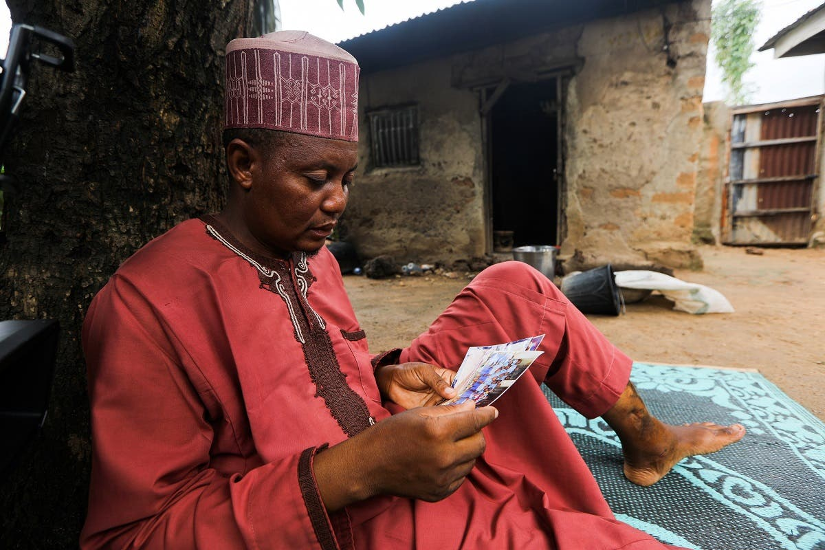 Aminu Salisu, a parent, looks at the pictures of one of the children kidnapped by bandits at Salihu Tanko Islamic school in Tegina, Niger State, Nigeria August 11, 2021. (Reuters)