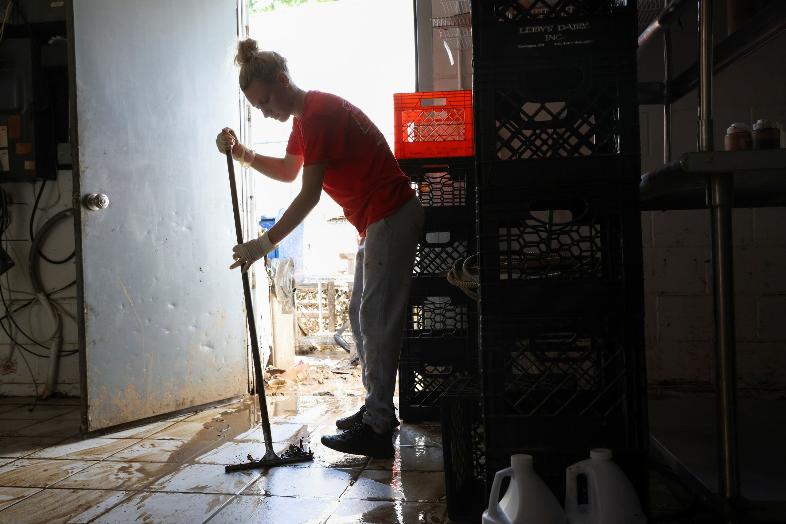 Kiana Jardot, manager of Four Boys Ice Cream, cleans mud and water left by flooding due to Tropical Storm Henri, in Jamesburg, New Jersey, US, August 23, 2021. (Reuters)