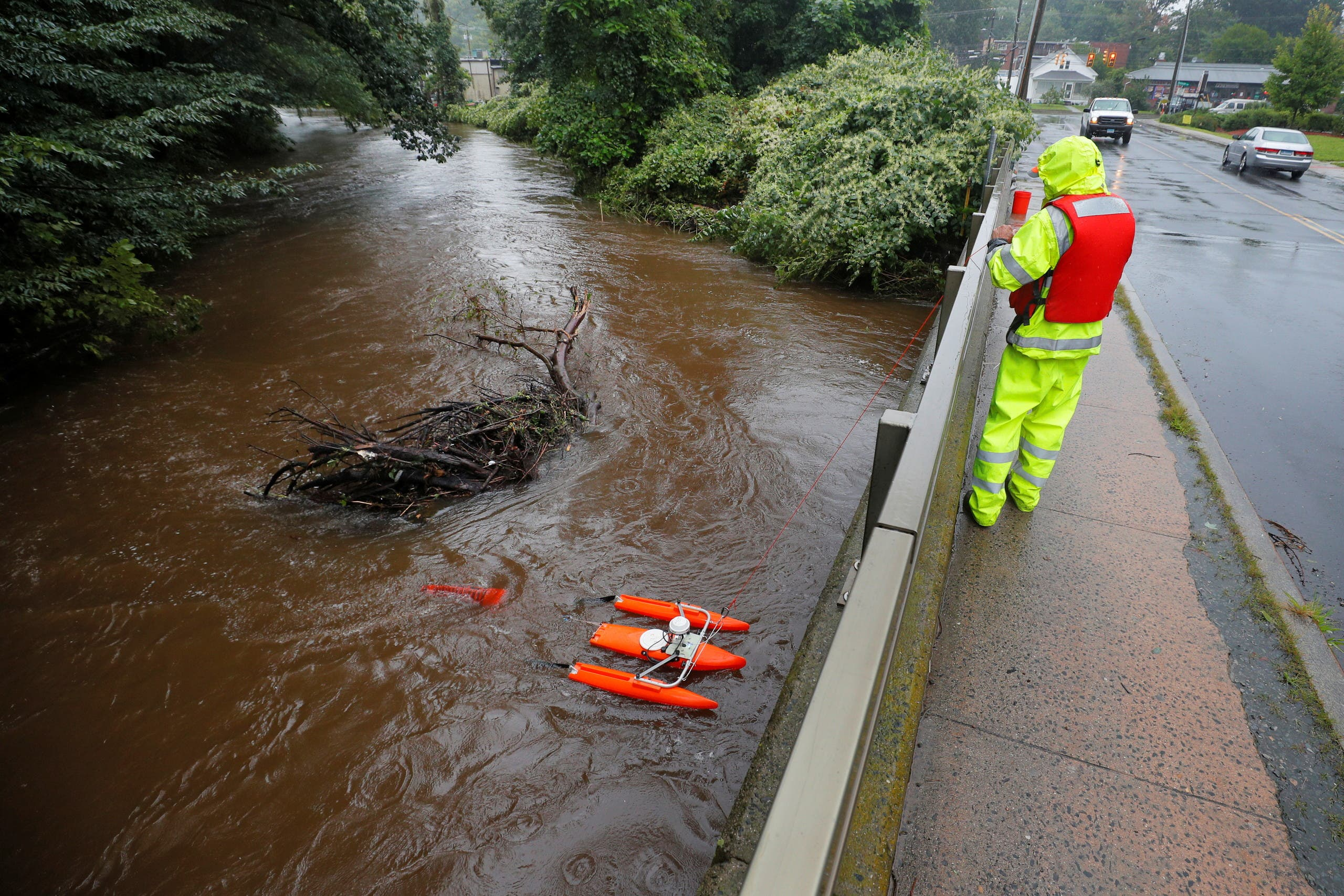 JR Bubicki, with the U.S. Geological Survey (USGS), uses a boat with sensors in the Hockanum River, swollen from the rains from Tropical Storm Henri, to measure the flow rate in East Hartford, Connecticut, US, August 23, 2021. (Reuters)
