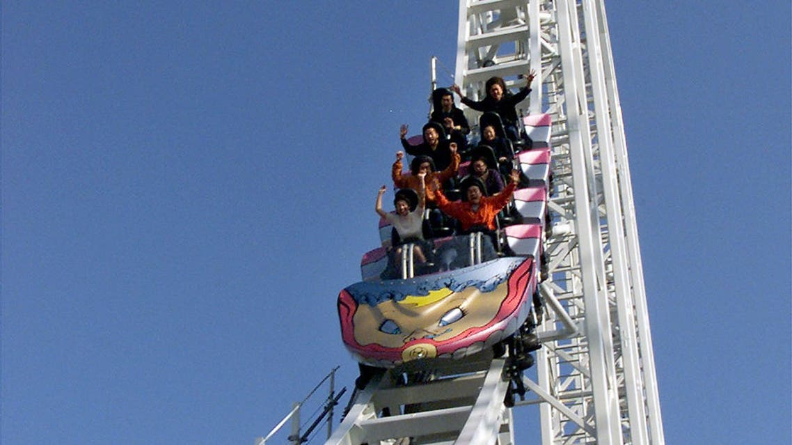 Guests raise their arms as they enjoy what is claimed to be the world's fastest roller-coaster called Dodonpaat Fujikyu Highland amusement park in Fuji-Yosida, west of Tokyo, December 3, 2001. The rides' top speed is 172-km per hour on the 1,200-metre track. The roller-coaster will be opened to the public at the end of December, 2001. Japan's Mt Fuji is seen in the background. REUTERS/Haruyoshi Yamaguchi